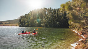 Kayakers гребя совместно на неподвижном озере Стоковые Фото