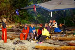Kayakers сидят вокруг огня слушая к гиду Стоковое Изображение