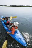 Kayakers. Back view of African American middle-aged couple paddling kayak Royalty Free Stock Photos