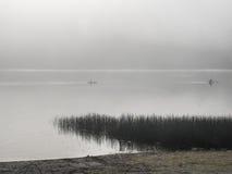 Kayakers auf einem nebeligen See Stockfotos
