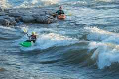 Kayakers at Brennan's Wave. Missoula, Montana: 01 July 2014 - Man kayaking Brennan's Wave on the Clark Fork River and another waiting to try royalty free stock photo