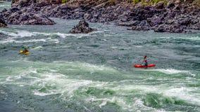 Kayakers che traversano attraverso le rapide dell'acqua bianca ed intorno alle rocce Immagini Stock Libere da Diritti