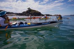Kayakers in den bunten Kajaks in der Gruppe durch Insel am ruhigen sonnigen Tag Stockbild