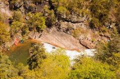 Kayakers, die über Wasserfall hinausgehen Stockfoto