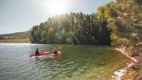 Kayakers, die zusammen auf ruhigem See rudern Stockfotos