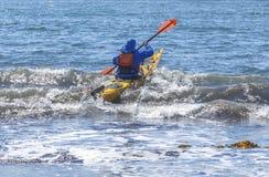 Kayakers en costa de la arena del Océano Pacífico Imágenes de archivo libres de regalías