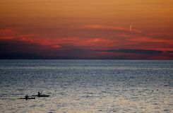Kayakers en la puesta del sol Fotos de archivo libres de regalías