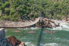 Kayakers entering the Storms River gorge. STORMS RIVER MOUTH, SOUTH AFRICA - FEBRUARY 29, 2016:  Unidentified kayakers passing underneath the suspension bridge Stock Photo