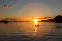 Kayakers in the glow of the setting sun on the ocean. Stock Photography