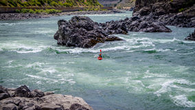 Kayakers navigating through the White Water Rapids and around Rocks. And Boulders in the Fraser River as the river  winds through the Fraser Canyon in British Royalty Free Stock Photo