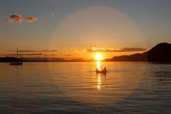 Kayakers no fulgor do sol de ajuste no oceano Fotografia de Stock