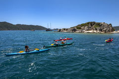 Kayakers paddle through the Mediterranean Sea off the coast of Turkey at Kalekoy. Stock Image
