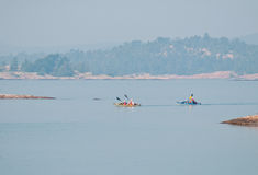 Kayakers paddling on a hazy day Stock Photos