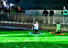 Kayakers schaufeln entlang dem Chicago River, der gefärbtes Grün für St- Patrick` s Tag ist, da Mengen Szene umgeben Stockbilder