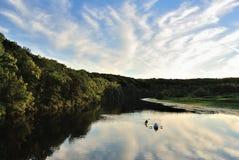 Kayakers on serene lake paddling Stock Photography