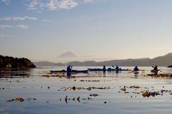 Kayakers silueteados por la luz de la mañana imagenes de archivo