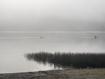 Kayakers su un lago nebbioso Fotografie Stock