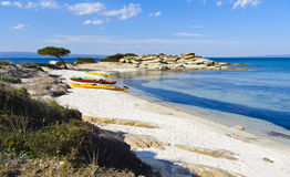 Kayaking adventure in paradise. Colorful kayaks on white sandy beach in bay in Greece royalty free stock image