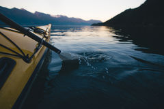 Kayaking alone on calm water with mountains in the background while sunset royalty free stock photo
