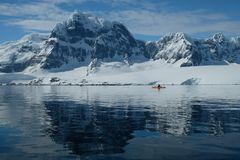 Antarctica orange kayak in a mirror blue bay beneath snow capped mountains royalty free stock photo