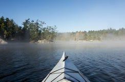 Kayaking avec le brouillard de matin Image stock