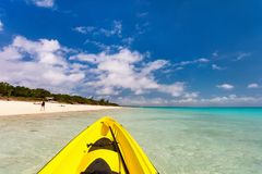 Kayaking at beautiful tropical beach. Colorful kayak at beautiful tropical beach with white sand, turquoise ocean water and blue sky Stock Images