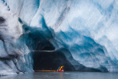 Kayaking into blue ice cave. In glacier iceberg, Alaska royalty free stock photography