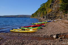 Kayaking on Cape Breton Island. A row of kayaks is lined up agains the Atlantic Ocean Shoreline on Cape Breton Island, Nova Scotia, Canada royalty free stock images