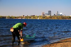 Kayaking at a city park. A Kayaker prepares to enter Lake Calhoun, with the Minneapolis, Minnesota skyline in the background Royalty Free Stock Image