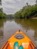 Kayaking on the Dan River. A kayaker floats on the calm, glassy surface of the Dan River near Danbury, North Carolina while storm clouds build above and darken royalty free stock image