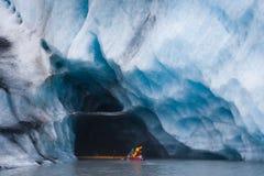Kayaking dans la caverne de glace bleue Photographie stock libre de droits