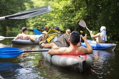 Kayaking. Group of friends relax on canoe in wild river. Sport tourism in jungle river. Leisure activity. Swim in kayak. People swimming in boats royalty free stock image