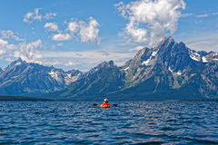 Kayaking Jackson Lake in Grand Teton National Park. A woman kayaker checks out the view of the Tetons on Jackson Lake in Grand Teton National Park in Wyoming Royalty Free Stock Images