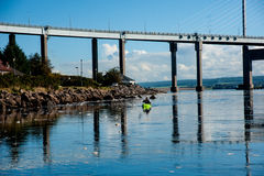 Kayaking beside Kessock Bridge. Kessock Bridge joining Inverness to Black Isle with Kayak traveling in calm waters stock images