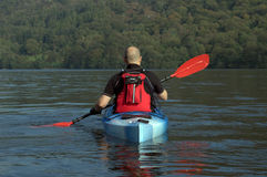 Kayaking on Lake Windermere. Male kayaker paddling away from the viewer on Lake Windermere England Stock Photo
