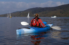 Kayaking on Lake Windermere. Female kayaker paddling away from the viewer on Lake Windermere England Royalty Free Stock Images