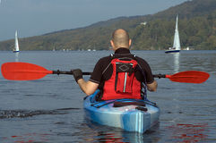 Kayaking on Lake Windermere. Male kayaker paddling away from the viewer on Lake Windermere England Royalty Free Stock Images