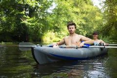Kayaking langs wilde rivier Twee mensen in boot Jonge mens met roeispanen in kano Vrije tijd op kajak Actief toerisme op aard in  royalty-vrije stock fotografie