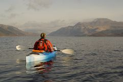 Kayaking on Loch Lomond. Female kayaker paddling away from the viewer on Loch Lomond with Ben Lomond mountain in the background Stock Photo