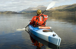 Kayaking on Loch Lomond. Female kayaker paddling away from the viewer on Loch Lomond with Ben Lomond mountain in the background Stock Photos