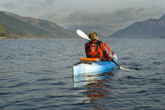 Kayaking on Loch Lomond. Female kayaker paddling away from the viewer on Loch Lomond with Ben Lomond mountain in the background Stock Image