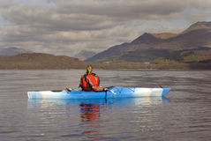 Kayaking on Loch Lomond. Female kayaker paddling away from the viewer on Loch Lomond with Ben Lomond mountain in the background Royalty Free Stock Photos