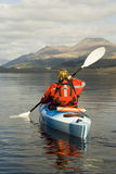Kayaking on Loch Lomond. Female kayaker paddling away from the viewer on Loch Lomond with Ben Lomond mountain in the background Stock Photography