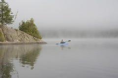 Kayaking on a Misty Lake. Man Paddling a Blue Kayak on a Misty Lake - Haliburton, Ontario stock photos