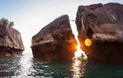 Kayaking near rocks royalty free stock photo