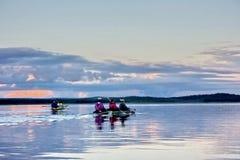 Kayaking på en sjö på solnedgången Arkivfoto