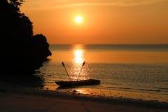 Kayaking på stranden med röd himmelsolnedgång Fotografering för Bildbyråer