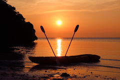 Kayaking på stranden med röd himmelsolnedgång Arkivfoton