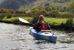 Kayaking on Padarn Lake. Female kayaker paddling away from the viewer on Padarn Lake Wales with Dolbadarn Castle in background - landscape orientation Royalty Free Stock Photos