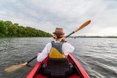 Kayaking podróż Młoda dama paddling czerwonego kajaka widok z powrotem Wakacje i lata przygoda Obraz Stock